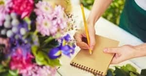 woman writing letter with flowers beside her