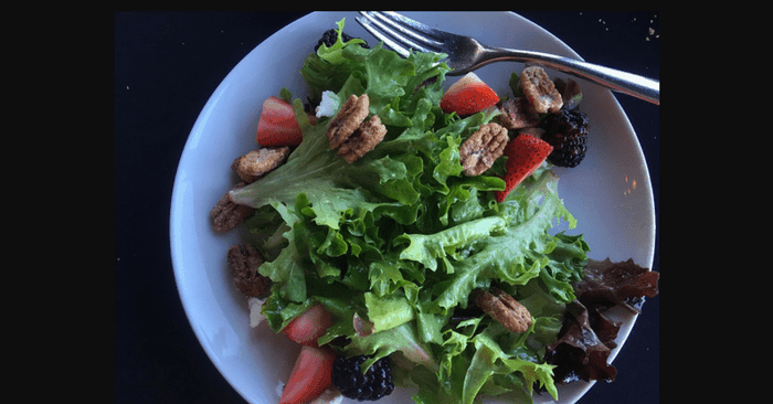 bowl of leafy dark green lettuce with pecans and strawberries