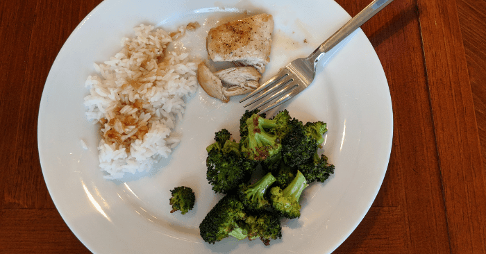 roasted broccoli, white rice with sauce, grilled chicken on white plate for high carb cycling day