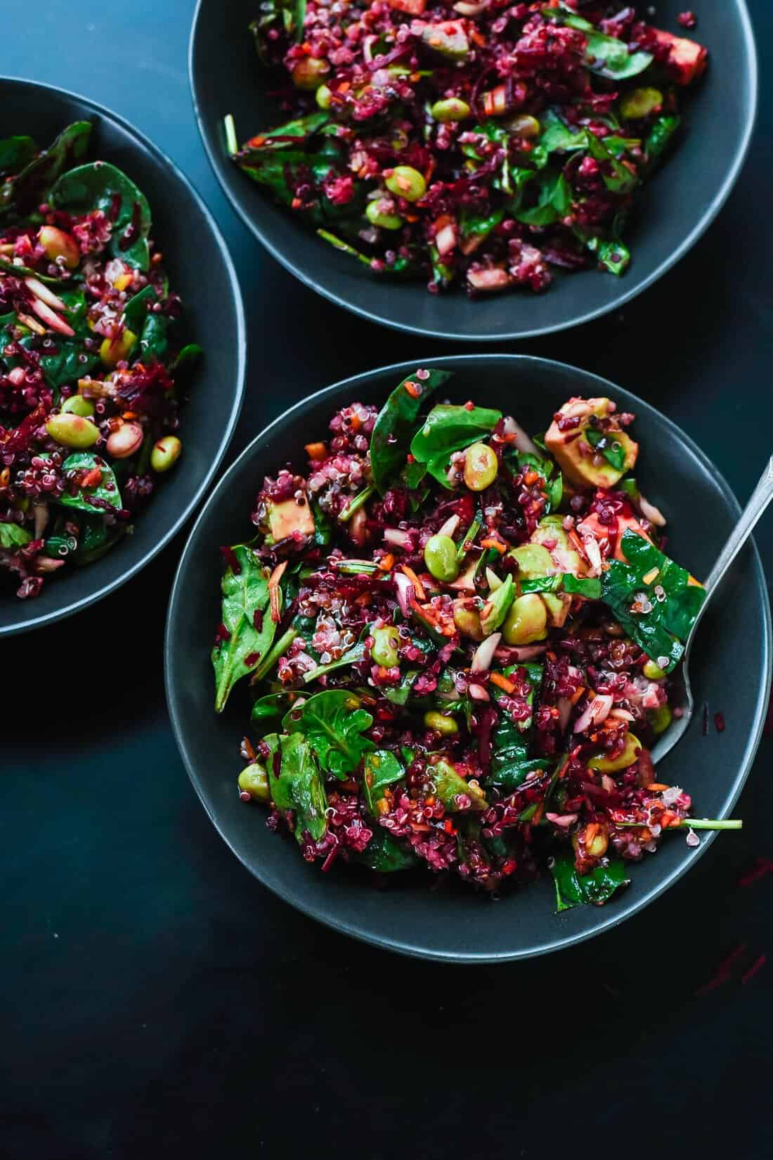 beets with quinoa, carrots and greens in a bowl