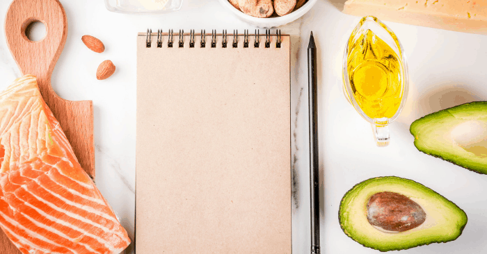 salmon and avocado healthy fats, notebook and pen to work on carb cycling to lose weight meal plan