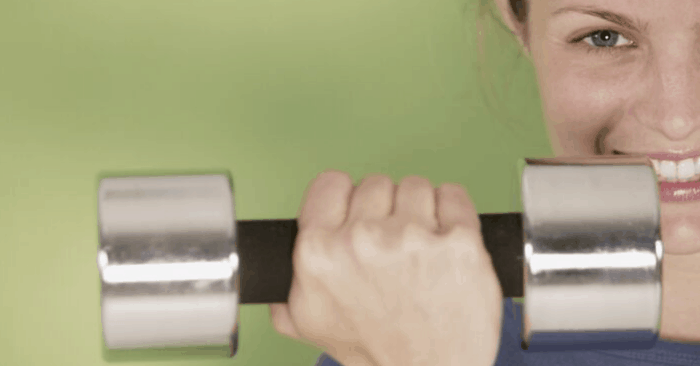 woman lifting weights with a weight in her hand smiling
