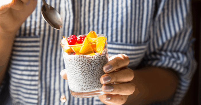 woman holding glass with soaked chia seeds and fruit