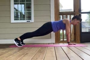 woman doing high plank shoulder taps