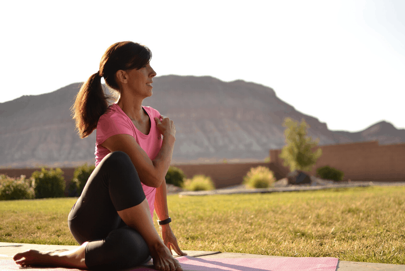 lady on yoga mat stretching outside with desert mountain in background