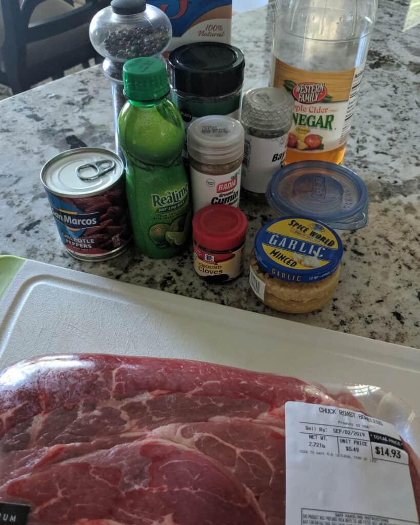 chuck roast, bottles and jars of ingredients needed to make beef barbacoa